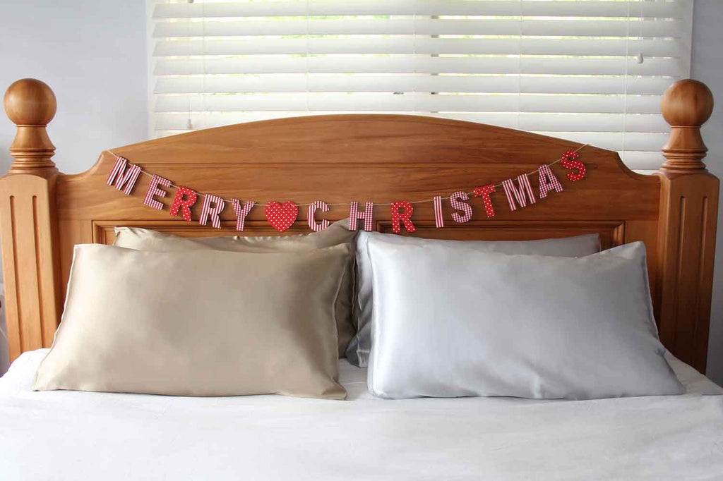 Gold and silver silk pillowcases nz with happy Christmas message on bed headboard