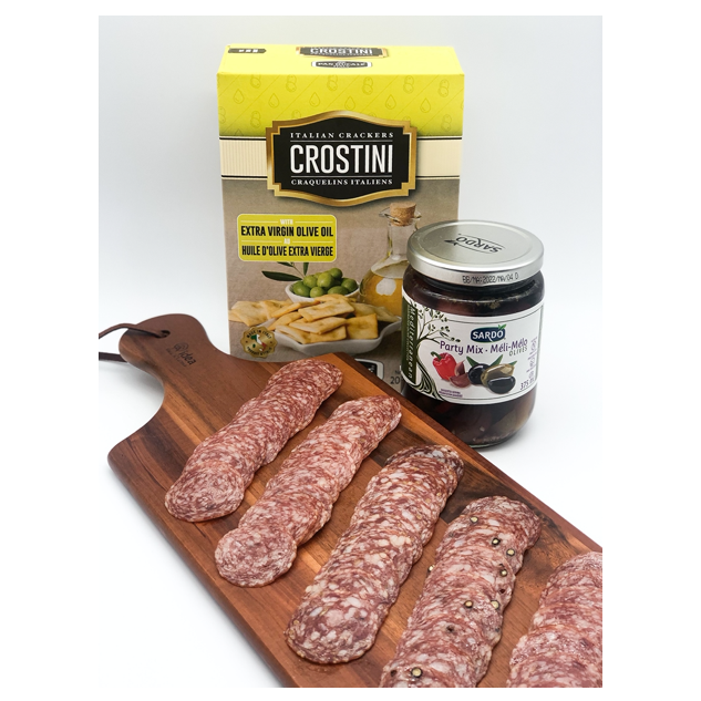 charcuterie meat sliced on wood board with a box of crackers and jar of mixed olives