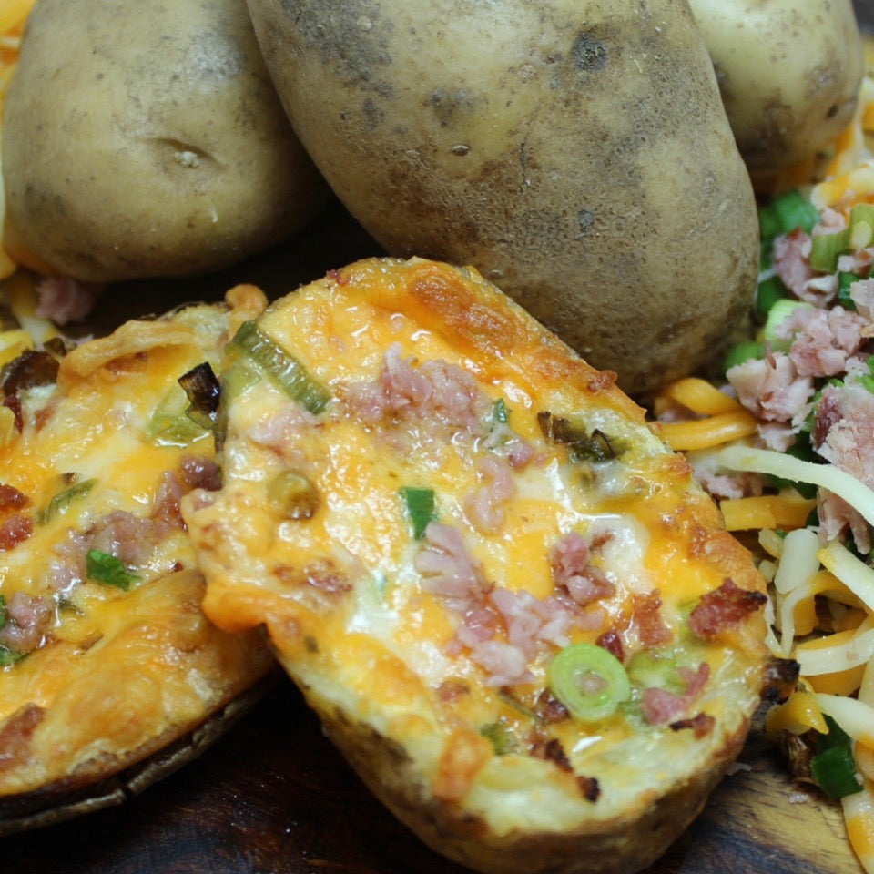 two cooked fully loaded potato skins