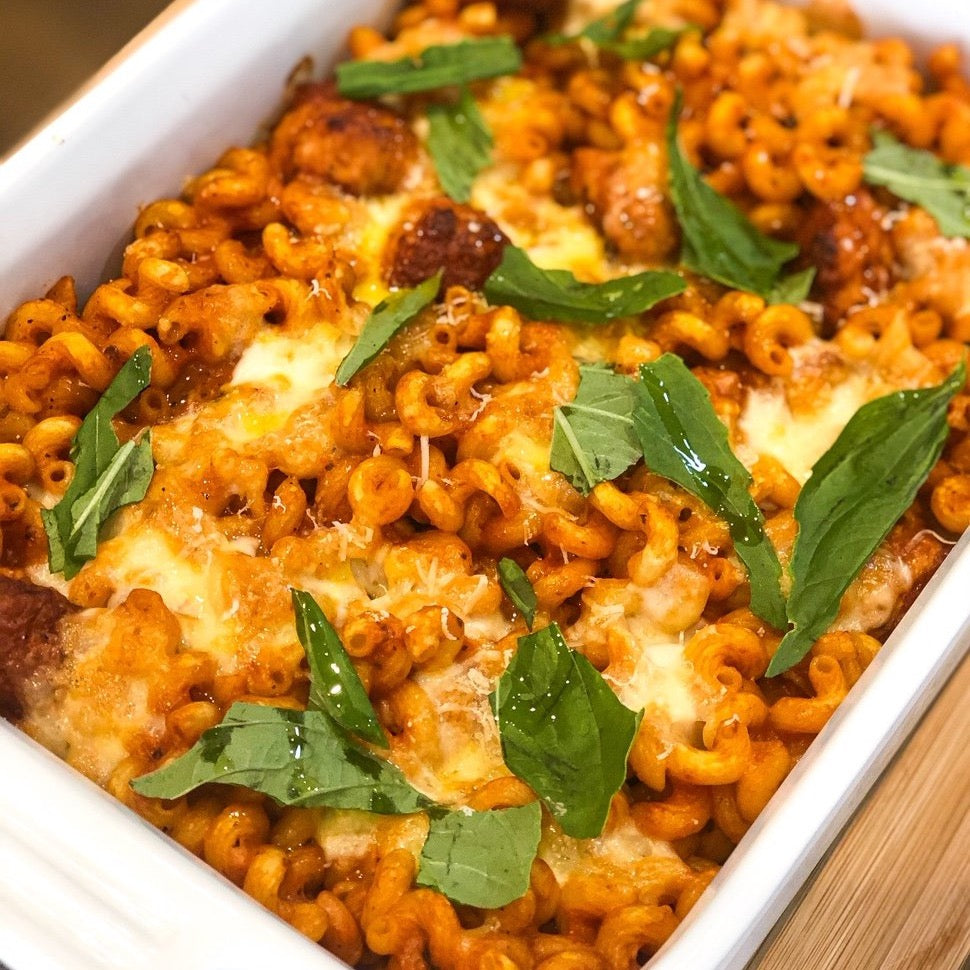 baked pasta dish with meatballs and topped with fresh basil