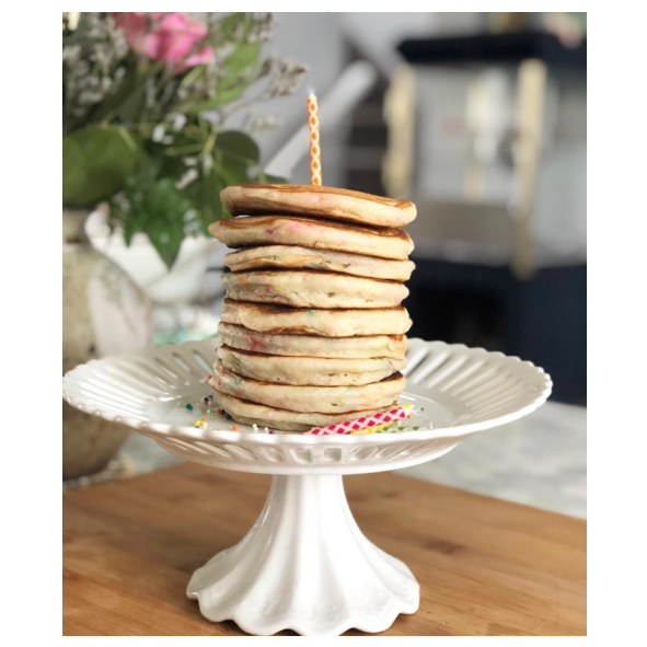 cooked stack of birthday cake pancakes with sprinkles in them and a candle on top