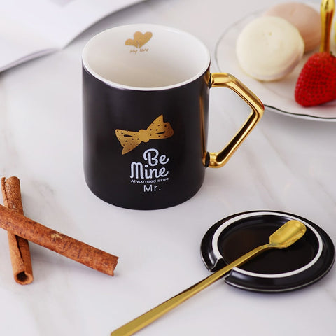 Black open coffee mug with the words Be Mine written in white with a gold bow tie above it placed on a table next to a black coffee mug lid and a gold spoon.