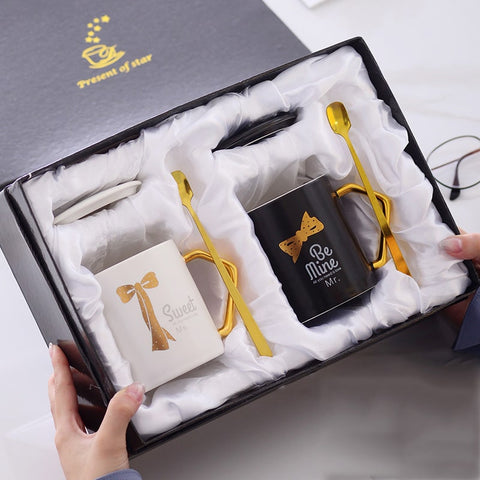 An open gift couples with two mugs placed in it. On the left is white coffee mug, with its matching lid, and gold plated spoon. On the right is a black coffee mug with its lid and spoon securely packaged. The mug has the words Be Mine written in white with a gold bow tie on top of it.