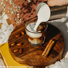 A glass with cold coffee is being filled with milk while sitting on a wooden waiter next to some coffee beans. Photo taken by Polina Kovaleva.