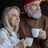 A photo of an elderly couple enjoying each other's company while drinking from their respective mugs.