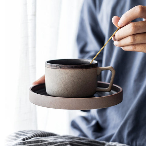 Stone colored coffee mug and saucer placed in the hands of someone wearing a light blue shirt.