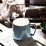 Blue-grey personal coffee mug with a unique handle having hot water poured into it.