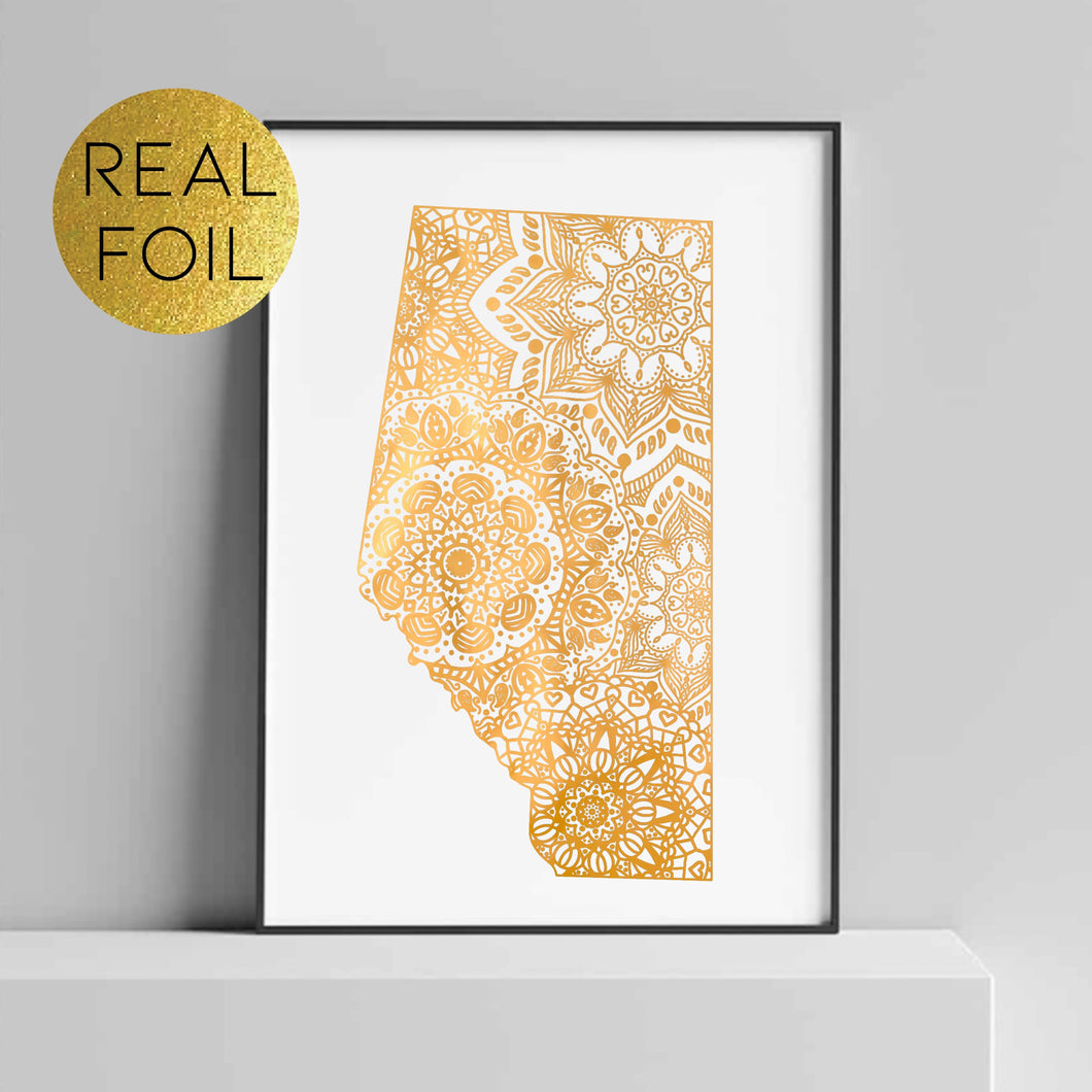 Grey background with a black picture frame, inside is a white art print with the picture being of a gold geometric design of Alberta, Canada