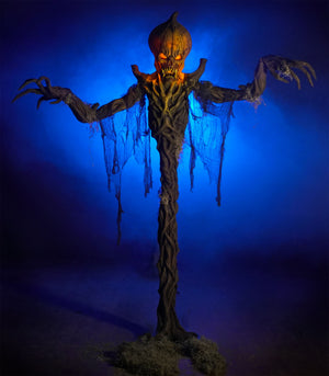 8 Ft tall Pumpkin Stalker Halloween prop decoration by Distortions Unlimited. Giant monster with creepy pumpkin head and long arms and fingers standing in blue fog.