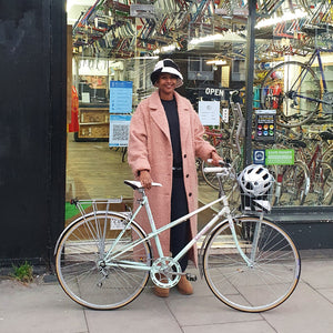 a smartly dressed woman stands in front of her local bike shop in Stoke Newington London she has a lovely Raleigh bicycle from the 1980s her eighties bike is made of steel so is strong and lightweight and should last her a lifetime