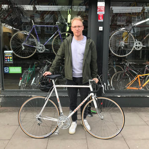 a happy customer stands in front of a renowned vintage bicycle shop in Stoke Newington London he is standing with his beautiful white Peugeot restored bike with many more options in the window of his local bike shop