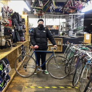 a warmly dressed customer is standing inside their local bike shop in Stoke Newington London where he has just picked up his new steel commuter bike that he hopes to get many years and many miles of enjoyment from