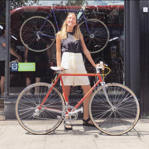 a woman stands in front of a local bike shop in Stoke Newington London it is summer and she has a new bike to enjoy rolling around on it is a bike from the seventies and is a rare Louis road bike with classic components