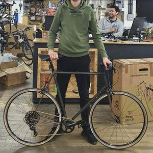 a large man stands with his new bike and steel frame lacquered so that the raw effect can be seen it has a 1 x 11 Sram Apex groupset with lovely tan wall Panaracer Pasela tyres the bike is really very lovely to look at and is situated in Stoke Newington