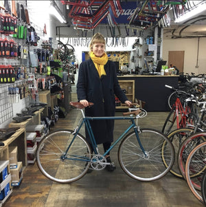 a loyal customer stands inside her local bicycle shop in Stoke Newington London her bicycle is a very rare Hetchins made of steel and produced very locally in Tottenham during the golden age of bicycle travel and manufacture