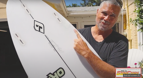 Ding All Dale holding a repaired Fire Wire surfboard. Dale is positioned outside under the sunshine and is smiling.