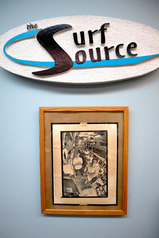 Surf Source article - Founders Story - Origins of surf board distribuler - DING ALL surfboard repair products. This is a photograph of Surf Source signage and frames newspaper article.