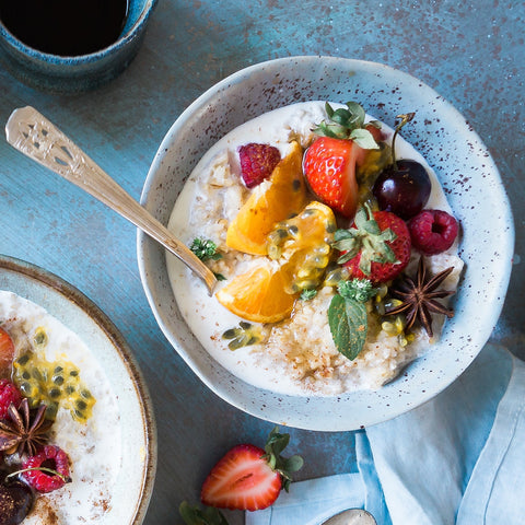 Vegan breakfast bowl with oats and fruit. On a blue table.