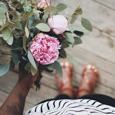 Woman holding pink peony flowers - peony is a natural herb to help with PCOS.