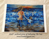 art print of mother walking towards the sun on the beach at the coast holding hands with a little boy walking with her