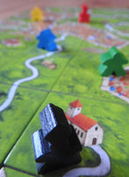 Close-up view showing a black abbot figure and several meeples on landscape tiles.