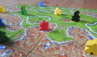 Wide view showing lots of meeples and abbots placed on the landscape tiles.