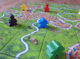 Close-up view of various meeples and abbots placed on the game tiles.
