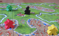 Another view of meeples and abbots placed down amidst cities, roads and monasteries depicted on the landscape tiles.