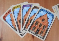 View of the backs of the cards in the five different colours - red, yellow, purple, brown and blue.