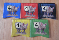 Close-up view of the 5 pig tokens in the different colours - blue, red, black, yellow and green.