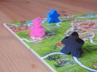 Close-up view of several of the meeple figures and an abbot piece.