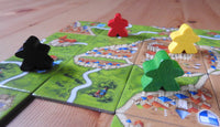 Close-up view of a number of meeple pieces shown on Carcassonne tiles.