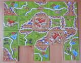 Top view of the 18 tiles included in this expansion, showing cities, monasteries, roads and cathedrals.