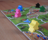 Close-up view of meeples and abbot figures shown on Carcassonne tiles.