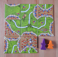 Top view of the 8 mage & witch tiles along with the purple mage meeple token and the orange witch meeple token.