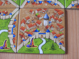 Close-up view of one of the tiles, showing the city with its walls, with the witch's hat symbol in the corner.