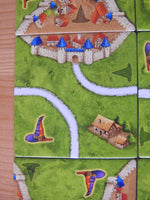 Close-up of another tile, with roads, a dwelling and city walls featuring.