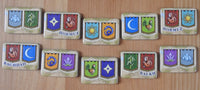 Close-up view of the 10 goal tokens included, featuring all the different city shields.