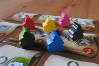Close up of the wooden mini messenger figures in their 8 colours: blue, green, black, red, yellow and pink.