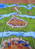 Close-up view of some of the tiles, showing the meandering river making its way around the settlements and fields of Carcassonne.