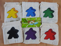 Top view showing all 6 Meeple bag colours and the 2 tiles and teacher meeple that come with this School Carcassonne Mini Expansion.