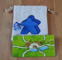 Close-up of the blue meeple bag, blue meeple teacher and 2 tiles.