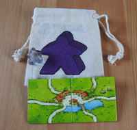 Close-up of the purple meeple bag, purple meeple teacher and 2 tiles.