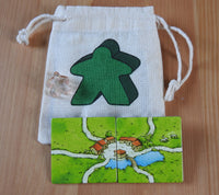 Close-up of the green meeple bag, red meeple teacher and 2 tiles.