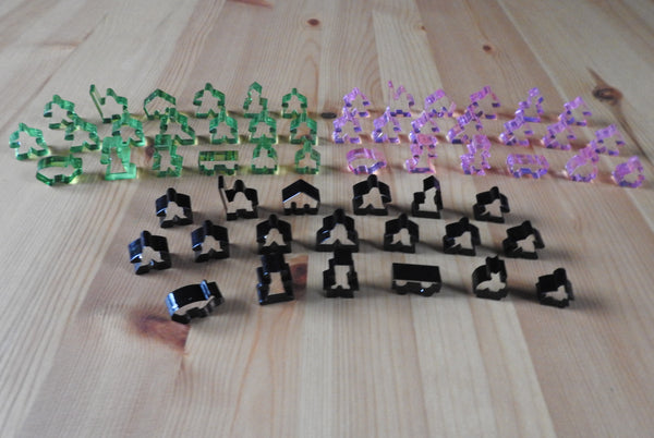 Top view showing 3 of the transparent meeple set colours - light green, pink and black.