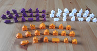 Top view of 3 of the differenet wooden meeple set colours available - orange, purple and white.