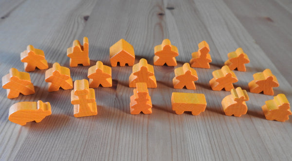 Close-up view of the orange wooden meeple set.