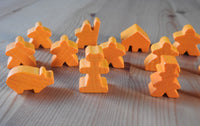 Close-up view of the orange pig, abbot and other meeple figures included.