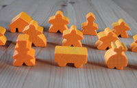 Close-up of the orange ringmaster and other meeples.