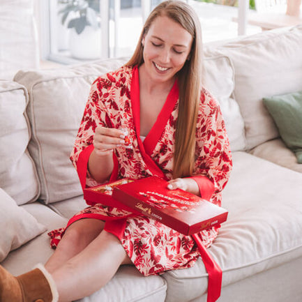 Eating chocolates in red rhea short robe
